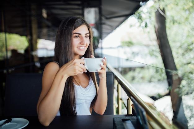 Открытый моды портрет красивой молодой девушки, пить чай кофе