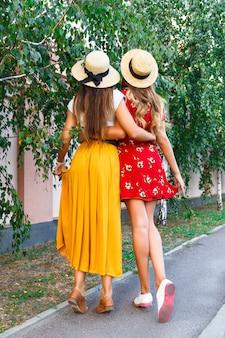 スタイリッシュなトレンディなヒップスターのレトロなドレスと帽子を身に着けている背中と抱擁の最高のガールフレンドの屋外ファッションポートレート。彼らの友情と素晴らしい時間を一緒に楽しんでください。
