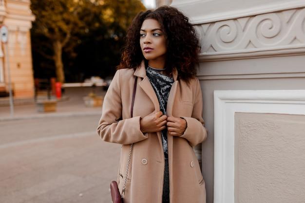 トレンディな秋の服、灰色のベルベットのセーター、ベージュのウールのコートを着て魅力的な官能的な若いスタイリッシュな黒人女性のアウトドアファッションの肖像画。