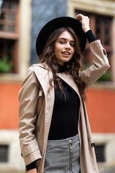 Открытый модный портрет гламурной чувственной молодой стильной дамы в модном осеннем наряде и черной шляпе на улице