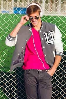Открытый модный портрет красивого парня в стильном весеннем спортивном наряде, слушающего любимую музыку
