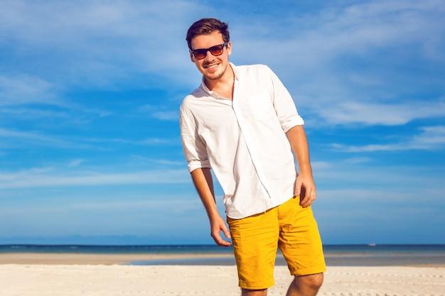 Открытый модный портрет красивого мужчины, позирующего на удивительном тропическом пляже, в хороший солнечный день, прекрасный вид на голубое небо и океан, в повседневной желтой классической белой рубашке и солнцезащитных очках.
