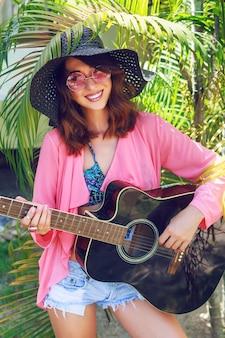 草に座って、アコースティックギターを持って幸せなかなり笑顔のヒッピー女のアウトドアファッションの肖像画。熱帯の暑い国、緑の背景。帽子とピンクのサングラスの夏の服装。