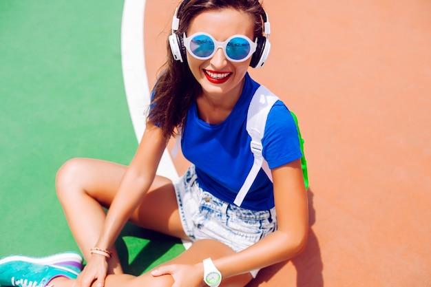 流行に敏感な女の子の明るい夏の服装でスポーツグラウンドでポーズ、音楽を聴く、スタイリッシュなスポーツシューズのバックパックとサングラスを身に着けている屋外ファッションポートレート。