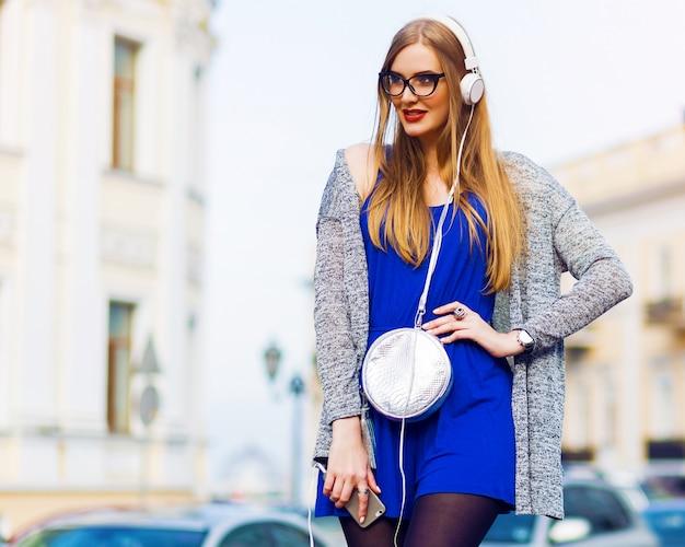 Внешний портрет моды стильной вскользь женщины с наушниками в голубых прозодеждах, серебряной сумки представляя против улиц. наслаждаясь прекрасной музыкой. летние солнечные краски.