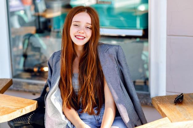 세련 된 생강 여자의 야외 패션 초상화, 화창한 날에 테라스 카페에서 포즈, 남자 친구 재킷, 밝고 신선한 색상을 입고.