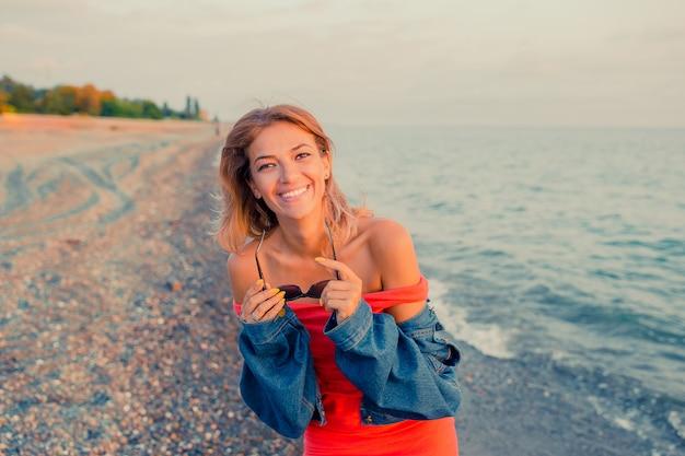 ビーチでトレンディなサングラスとジーンズジャケットを着てスタイリッシュな女の子のアウトドアファッションの肖像画。手を挙げて、レトロなフィルター、日光の斑点