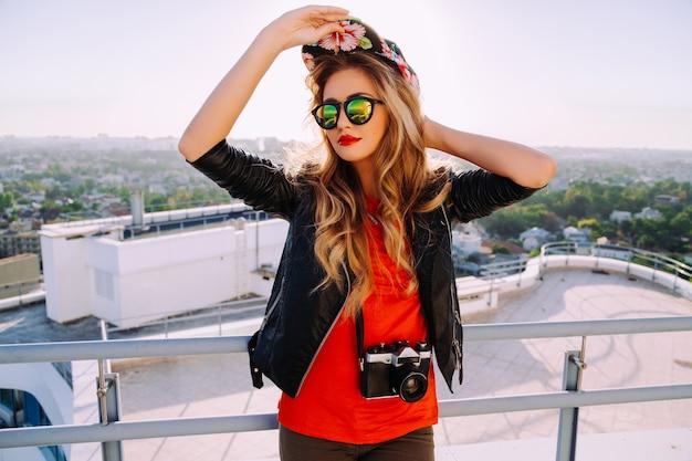 ヴィンテージのレトロなカメラを保持し、明るい盗品の帽子、流行のサングラスと革のジャケットを身に着けているスタイリッシュな写真家の女の子の屋外ファッションの肖像画、屋根からの街の素晴らしい景色