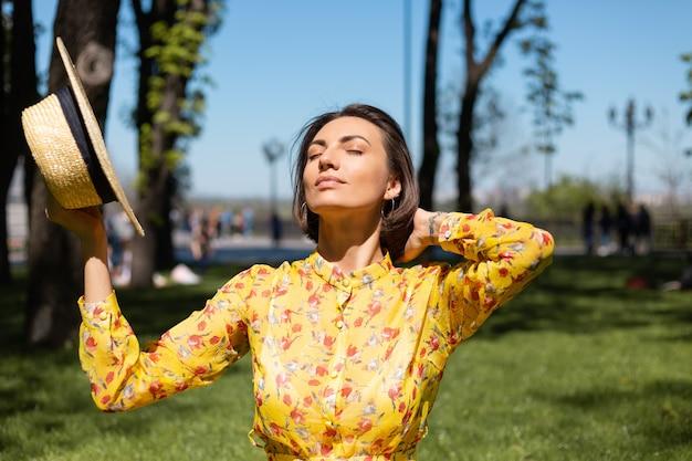 Открытый модный портрет женщины в желтом летнем платье и шляпе, сидящей на траве в парке