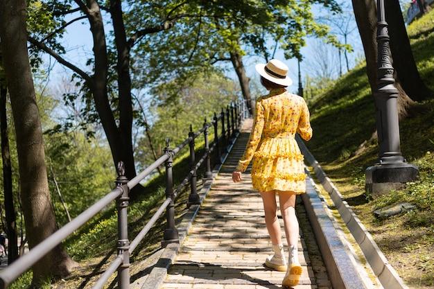 Открытый модный портрет женщины в желтом летнем платье и шляпе, идущей по тропинке в парке, вид сзади