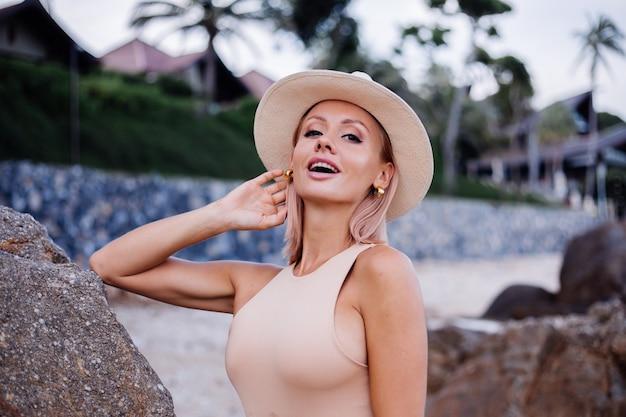 베이지 색 바디 슈트 블루 진 반바지와 열대 바위 해변 따뜻한 석양 빛에 고전적인 세련된 모자에 젊은 유럽 여자의 야외 패션 초상화