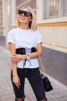 通りで晴れた日にかなり金髪の若い女性のアウトドアファッションの肖像画。屋外のサングラスの女の子。サングラスで幸せなファッションの女性。夏のトレンディな女の子の笑顔。