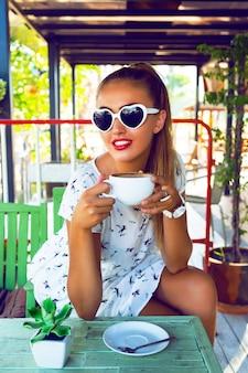 Открытый модный портрет молодой красивой девушки с красивыми большими клеевыми глазами, одетой в стиль булавки и макияжем, наслаждается своим прекрасным утром с чашкой кофе на террасе потертого шикарного кафетерия.