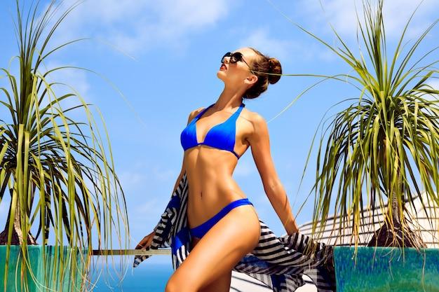 완벽한 슬림 피트 검게 그을린 몸을 가진 젊은 섹시한 모델 여성의 야외 패션 초상화, 비키니와 선글라스를 착용하고 고급 빌라에서 여름 휴가를 즐기고 섬 바다의 놀라운 전망을 즐기십시오.
