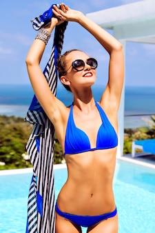 완벽한 슬림 피트 검게 그을린 몸을 가진 젊은 섹시한 모델 여성의 야외 패션 초상화, 비키니와 선글라스를 착용하고 럭셔리 빌라에서 여름 휴가를 즐기고 수영장과 섬 바다에서 놀라운 전망을 즐기십시오.
