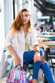 Открытый модный портрет молодой стильной потрясающей женщины, одетой в джинсы и элегантное пальто, гламурный яркий макияж, позирует на террасе городского кафе, путешествующий клон, солнечный день.
