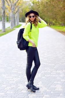 レザーパンツネオングリーンセーター、バックパックのヴィンテージの帽子とサングラスで通りでポーズをとって若いスタイリッシュな女性のアウトドアファッションの肖像画。ストリートスタイルに見える。