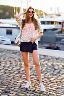 Outdoor fashion portrait of pretty blonde woman walking alone at nice sunny autumn day, cozy swather mini skirt, evening sunlight.