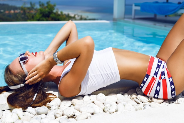 Outdoor fashion portrait of stunning woman with perfect body, relaxing near pool with amazing view on ocean and tropical island, enjoy the music on earphones, wearing sexy summer outfit.