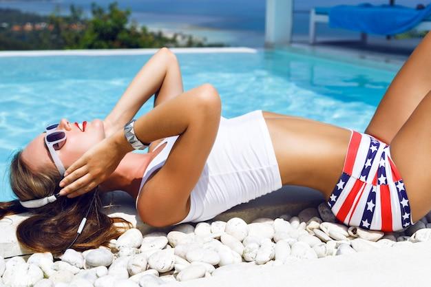 Ritratto di moda all'aperto di splendida donna con un corpo perfetto, rilassante vicino alla piscina con splendida vista sull'oceano e sull'isola tropicale, godersi la musica con gli auricolari, indossare abiti estivi sexy.