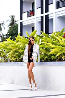 Ritratto di moda all'aperto di giovane donna castana alla moda che posa vicino a palme e indossa un vestito bianco e nero alla moda moderno
