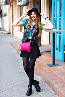 Outdoor fashion portrait of stylish sexy woman walking alone, stylish outfit, mini skirt, black hat and biker jacket, bright fashion details, positive mood, summertime, street style, city center.