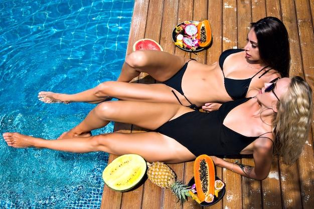 Открытый модный портрет двух симпатичных подруг-девушек, весело проводящих время, лежа и расслабляясь возле вечеринки у бассейна, держа в руках сладкие тропические фрукты, сексуальное бикини, солнцезащитные очки, веселую компанию, загорая.