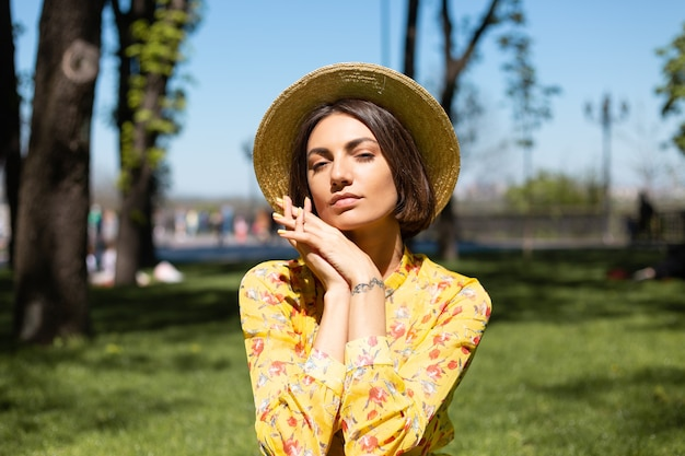Outdoor fashion portrait of woman in yellow summer dress and hat sitting on grass in the park
