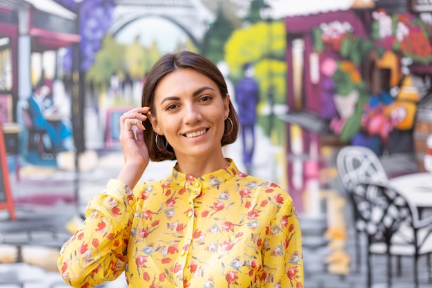 Outdoor fashion portrait of woman in yellow summer dress on street colourful wall