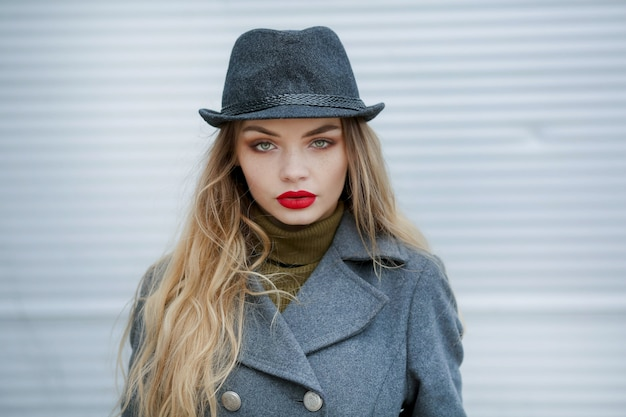 Outdoor fashion portrait of young beautiful fashionable woman wearing stylish accessories.vintage hat,looking at camera. female fashion beauty and advertisement concept. close up. copy space for text.