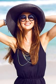 Ritratto di moda all'aperto di giovane donna sorridente graziosa felice, divertirsi sulla spiaggia, indossando cappello e occhiali da sole vestito elegante pulcino boho, umore positivo