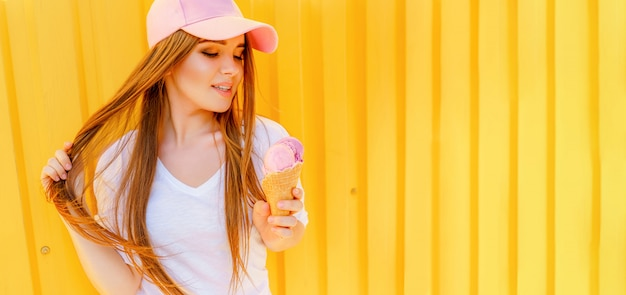 Outdoor fashion portrait of young hipster woman with ice-cream on yellow wall