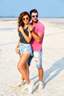 Outdoor fashion portrait of young pretty couple in love posing at amazing beach, wearing bright stylish casual clothes and sunglasses, enjoy their summer vacation near ocean.