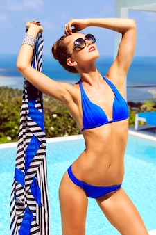 Outdoor fashion portrait of young sexy model woman with perfect slim fit tanned body, enjoy her summer vacation on luxury villa, amazing view on pool and island ocean, wearing bikini and sunglasses.