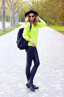 Outdoor fashion portrait of young stylish woman posing in the street in leather pants neon green sweater, backpack vintage hat and sunglasses. street style look.