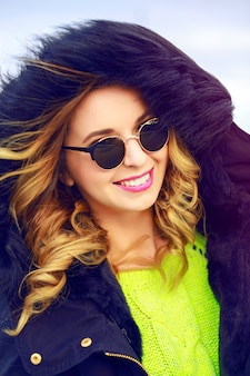 Outdoor fashion portrait of young stylish woman wearing worm hake and sunglasses