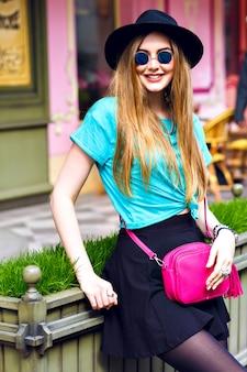 Ritratto positivo alla moda all'aperto di ragazza alla moda hipster, lunghi capelli biondi, cappello vintage, vestito luminoso in stile street, in posa vicino a un grazioso caffè francese, gioia, viaggio, vestito.