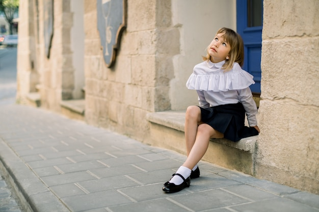 Outdoor fashion street city portrait of little caucasian girl. happy little girl sitting near the old building wall in ancient european city with blue door on the background