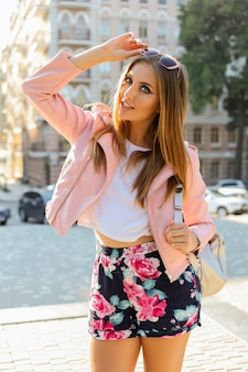 Outdoor fashionable portrait of blond woman posing  on the street. wearing stylish sunglasses, pink leather jacket and back pack.