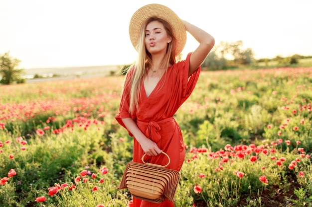 Outdoor fashionable portrait of stunning blonde woman  posing while walk in  amazing poppy field in warm summer evening.  wearing straw hat, trendy bag and red dress.