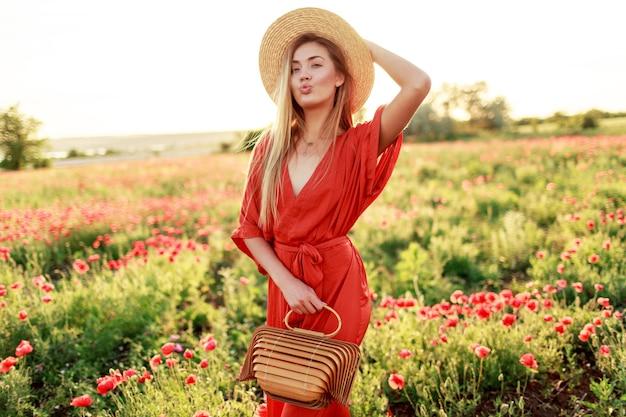 Ritratto alla moda all'aperto di splendida donna bionda in posa mentre si cammina in un incredibile campo di papaveri in una calda sera d'estate. indossa un cappello di paglia, una borsa alla moda e un vestito rosso.