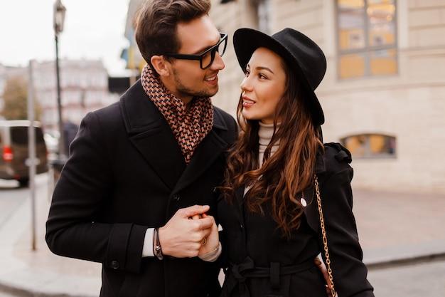 恥ずかしがり屋でお互いを見つめ合う恋愛のアウトドアファッショナブルでスタイリッシュなカップル。スカーフとコートで彼女のボーイフレンドとウールの帽子のブルネットの女性。