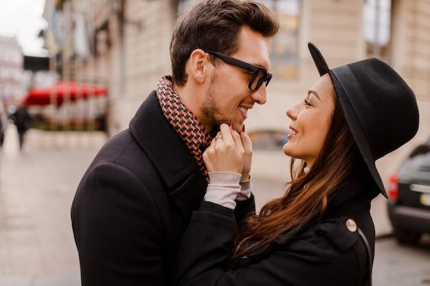 부끄러워하고 사랑으로 서로를 찾고 사랑에 야외 유행 세련된 커플. 스카프와 코트에 그녀의 남자 친구와 모직 모자에 갈색 머리 여자.