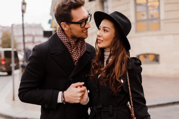 Outdoor fashionable stylish couple in love embarrassing and looking on each other with adore. brunette woman in wool hat with her boyfriend in scarf and coat.