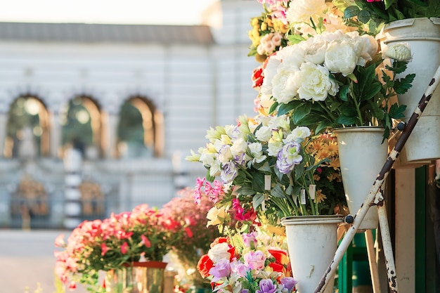 Outdoor flower market with roses, peonies and lilies. fresh flowers street shop in historic downtown. milan, italy