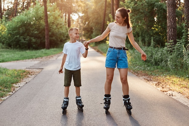 Outdoor full length portrait of happy brunette female holding son's hand and rollerblading together, family wearing casual style clothing, spending time in park.