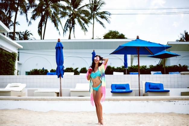 Открытый портрет в полный рост красивой очаровательной довольной дамы с стройной фигурой, позирующей на роскошном тропическом островном курорте, в винтажных тонах, в одежде в стиле бохо.