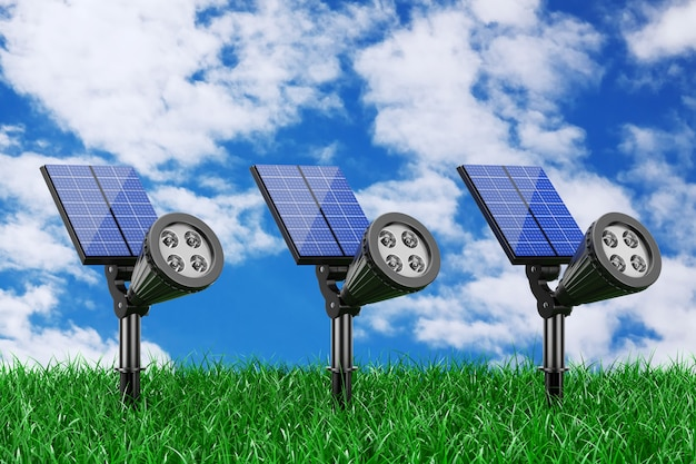 Outdoor garden led spotlights with solar panel in grass on a blue sky background. 3d rendering.