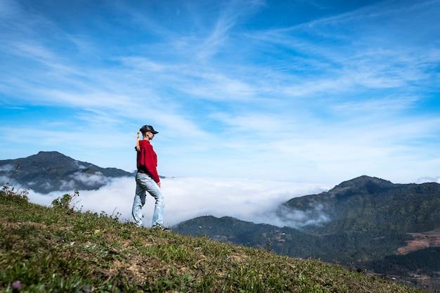 屋外の女の子は山頂を歩き、山脈の頂上をよく眺め、遠くを眺め、天気の良い日には旅行をします。若い女性は山の低い雲の背景に立っています。