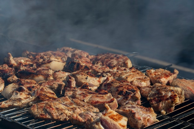 Outdoor grilling meat. beef or pork steaks on grill with smoke. barbecue in the nature.close up. soft focus.